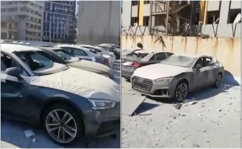 Cette image montre un parking d'un concessionnaire dans la ville avec des véhicules Audi endommagés qui étaient prêts à être livrés aux clients.